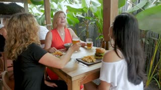 Three attractive multi ethnic group of women celebrating and cheering with drinks in a restaurant or bar pub in slow motion