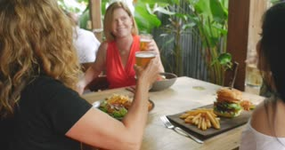 Three attractive multi ethnic group of women laughing and celebrating with a meal and drinks in glasses at a restaurant or bar pub