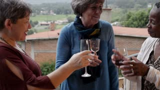 Three beautiful vibrant diverse mixed racial elderly senior women cheering with wine glasses outside on a balcony at their vacation home in slow motion