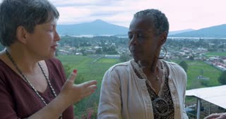 Three mixed racial female friends over 60 talking outside overlooking a mountain view