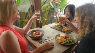 Three multi ethnic beautiful happy laughing women cheering and celebrating in a restaurant or bar pub with drinks in slow motion - stabilized shot