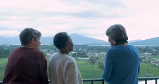 Three older women vacationers in their 60s talking at an scenic overlook