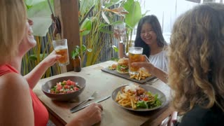 Three women from different countries laughing and celebrating with drinks in slow motion - stabilized shot