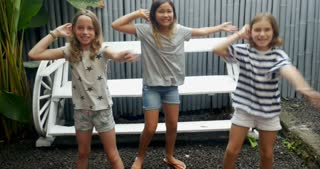 Three young diverse racial group of young pre teen girls dancing together smiling, laughing, and having fun