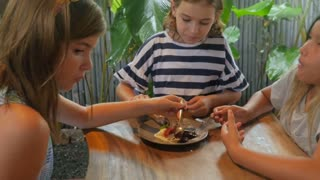Three young multi racial friends sharing a plate of lava cake dessert and vanilla ice cream in slow motion