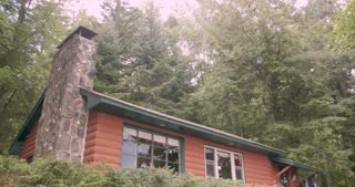 Tilt down establishing shot of a log cabin in the woods surrounded by trees and a forest