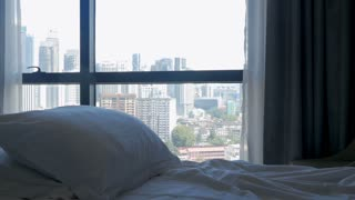 Tilt down of a bed with comfortable pillows and a modern city with tall buildings