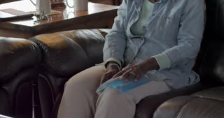 Tilt up of an elderly senior black woman in her 50s or 60s using an ice pack on her knee to relieve pain and swelling in her home