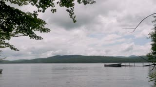 Time lapse of clouds moving away from the camera overlooking a lake, mountains, a boat, and a small floating dock