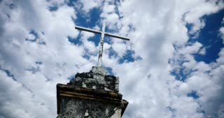 Time lapse of the clouds moving by an old cross against a blue sky - color graded