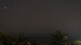Time lapse of the night sky overlooking the Pacific Ocean near Manzanillo Mexico with freight ships and palm trees in the background