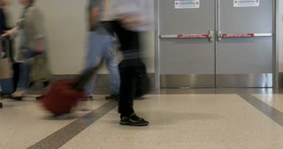 Time lapse of traveling people walking with their carry on luggage in an airport