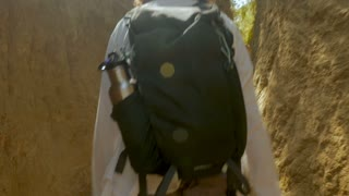 Tourist man hiking with a small backpack and metal water bottle on a well worn sandy trail with high walls in slow motion