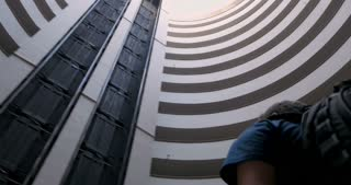 Traveling man wearing a backpack looking up at the sky through round futuristic building while the camera circles around him