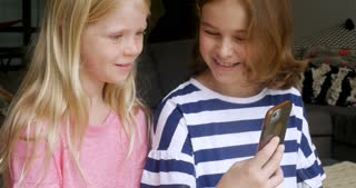 Two adorable happy and smiling young girls using a smart phone together and responding to a message by typing on the phone