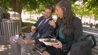 Two attractive businesspeople eating healthy food at lunch watching a digital tablet together and talking outside on a park bench in slow motion stabilized shot