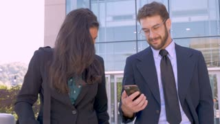Two attractive contemporary businesspeople walking and looking up from a cell phone smiling and laughing outside a business building in slow motion