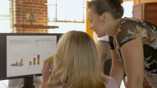 Two beautiful women reviewing data charts and graphs on a computer screen in a modern entrepreneurial business startup in slow motion stabilized shot