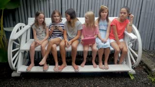Two cliques of young girls age 7 - 12 one happy one bored sitting on a long bench