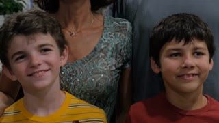 Two cute pre-teenage boys age 10 - 12 smiling and standing next to their parents for a portrait while laughing and giggling