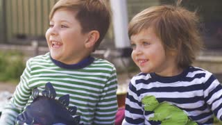 Two excited young children sitting, smiling and looking in anticipation outside in slow motion
