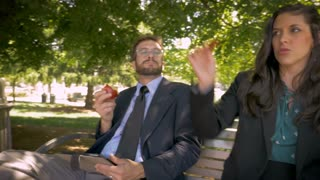 Two happy attractive millennial 30s businesspeople silly dancing while sitting with a digital tablet and eating healthy whole organic food for lunch outside on a park bench in slow motion