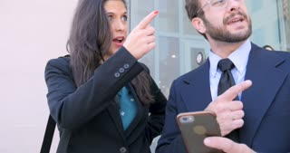 Two happy smiling millennial businesspeople looking at mobile phone technology, shaking hands and leaving outside a modern glass office building in 4k