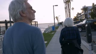 Two healthy baby boomers walking on beach path in urban setting. Active retired couple exploring waterway.