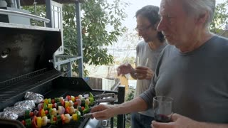 Two men, a man in his 40s and a senior man in his 70s cooking grilled vegetable kebabs and potatoes outside on a BBQ together in slow motion