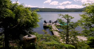 Two people relaxing on a dock along a mountain lake with a sun dial in view in the foreground - dolly shot