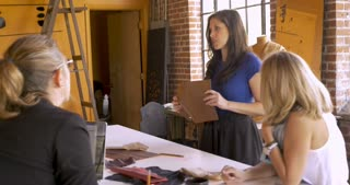 Two professional women designers demonstrating their ideas with samples to their coworkers in an open entrepreneurial startup workplace setting - stabilized shot