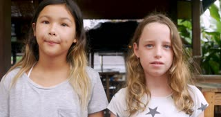 Two shy awkward young girls standing next to each other waiting