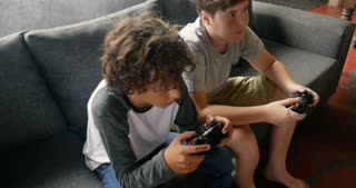 Two young 11 - 13 year old boys sitting on a sofa playing video games - stabilized shot
