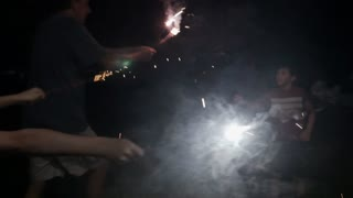 Two young boys aged 8 and 10 playing with sparklers with their father at night celebrating 4th of July Independence day holiday in slow motion