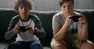 Two young boys playing video games together and getting to the finish line like they are playing a racing or driving game on a rainy day