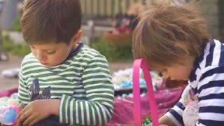 Two young children playing with toys in a basket outside together in slow motion