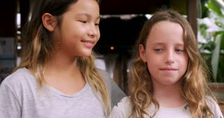 Two young girls smiling with their arms around each other's shoulders like they are best friends looking at the camera
