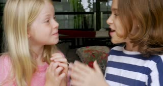 Two young happy smiling girls whispering and telling secrets to each other