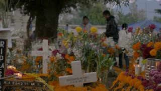 TZURUMUTARO, MEXICO - NOVEMBER 1, 2016 - Cross and grave markers in a Mexican graveyard with people decorating individual grave sites during day of the dead