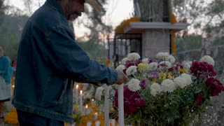 TZURUMUTARO, MEXICO - NOVEMBER 1, 2016 - Dolly shot of an old Mexican man lighting a candle at a graveyard alter during day of the dead
