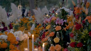 TZURUMUTARO, MEXICO - NOVEMBER 1, 2016 - Dolly shot of flower bouquets, candles, and people busy at graves during day of the dead