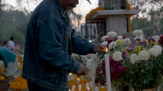 TZURUMUTARO, MEXICO - NOVEMBER 1, 2016 - Friendly people greeting each other while an old man lights candles at a graveyard alter during day of the dead