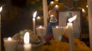 TZURUMUTARO, MEXICO - NOVEMBER 1, 2016 - Katrina figurine, photo of a deceased woman, and candles at a grave during day of the dead
