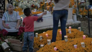 TZURUMUTARO, MEXICO - NOVEMBER 1, 2016 - Little Mexican boy helping his mother and grandmother at Day of the Dead