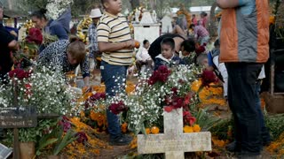 TZURUMUTARO, MEXICO - NOVEMBER 1, 2016 - Mexican family members decorating the graves of their ancestors celebrating the Mexican holiday Day of the Dead outside of Patzcuaro, Michoacan