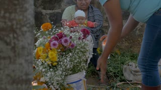 TZURUMUTARO, MEXICO - NOVEMBER 1, 2016 - Mexican woman holding a newborn baby giving instructions to another woman decorating a grave with flowers during day of the dead