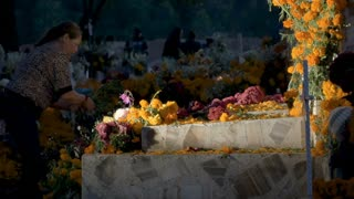 TZURUMUTARO, MEXICO - NOVEMBER 1, 2016 - Middle aged Mexican woman setting up flowers on a tomb in a graveyard during day of the dead dolly shot