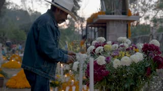 TZURUMUTARO, MEXICO - NOVEMBER 1, 2016 - Old Mexican man in a cowboy hat lighting candles at an alter at a graveyard during day of the dead