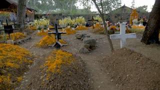 TZURUMUTARO, MEXICO - NOVEMBER 1, 2016 - POV walking through a cemetery near Patzcuaro, Michoacan decorated with flowers for Dios de los Muertos Day of the Dead