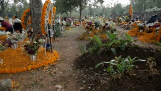 TZURUMUTARO, MEXICO - NOVEMBER 1, 2016 - POV walking through the beautifully decorated graves and alters for Mexican holiday Day of the Dead outside of Patzcuaro, Michoacan